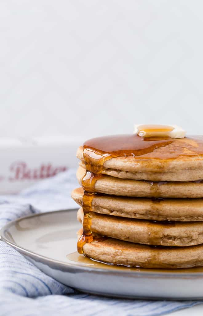 A stack of whole wheat pancakes on a plate, topped with butter and syrup.