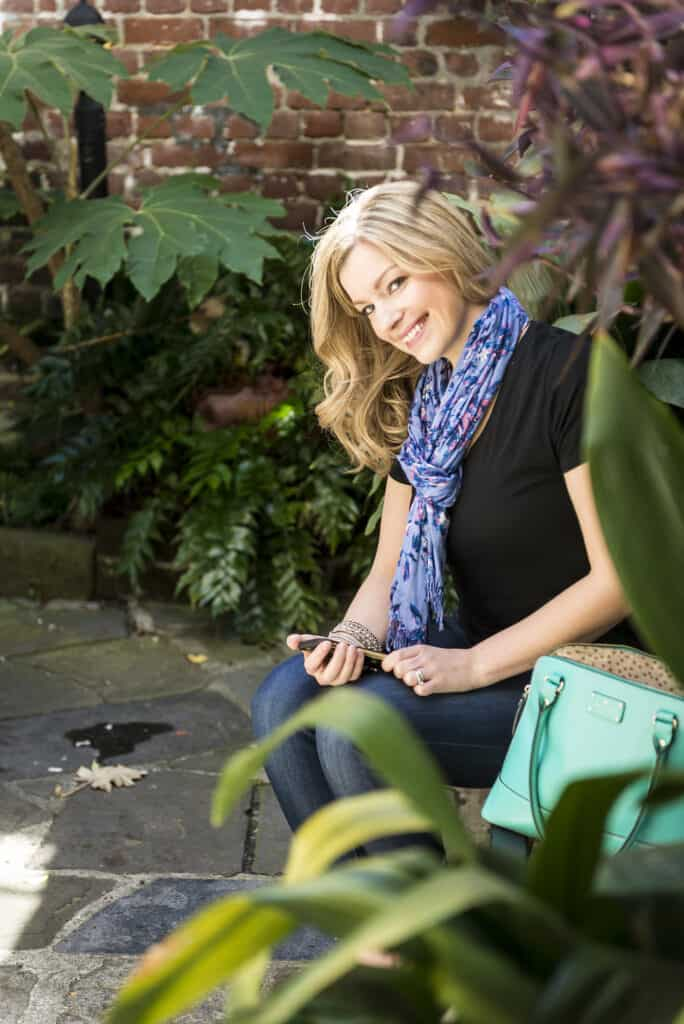 Image of woman in black shirt with a blue scarf, sitting on a bench outside, holding cellphone and looking towards camera.