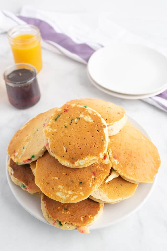 A messy stack of pancakes piled on a plate. Orange juice and syrup are also pictured.