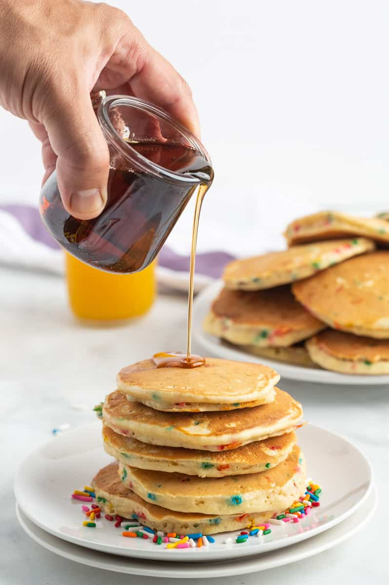 Syrup being poured on a stack of funfetti pancakes.