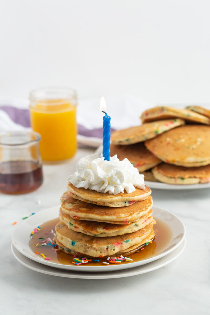 A stack of funfetti pancakes on a plate, topped with syrup, sprinkles, whipped cream, and a blue candle. More pancakes are pictured in the background.