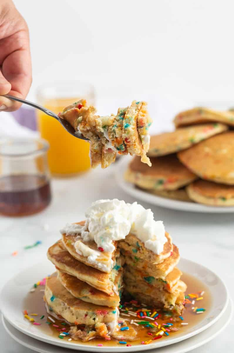 Stack of birthday cake pancakes with a slice out of them to show the sprinkles on the inside.