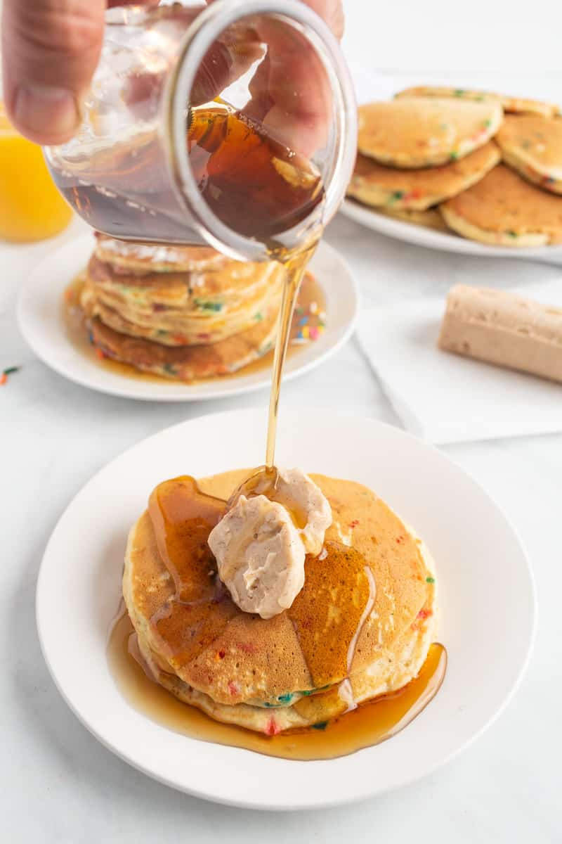 Syrup being poured on pancakes topped with two tabs of flavored butter.