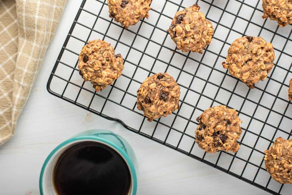Cookies on a cooling rack with a cup of coffee nearby.