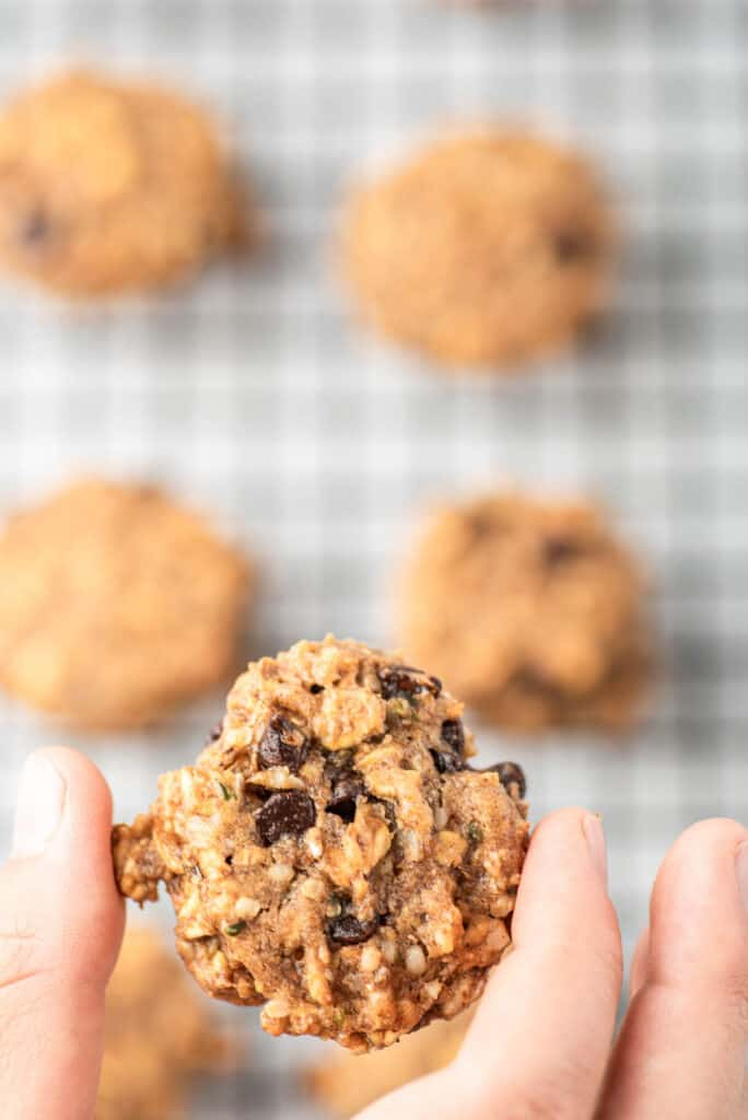 A hand holding a breakfast cookie over other cookies.