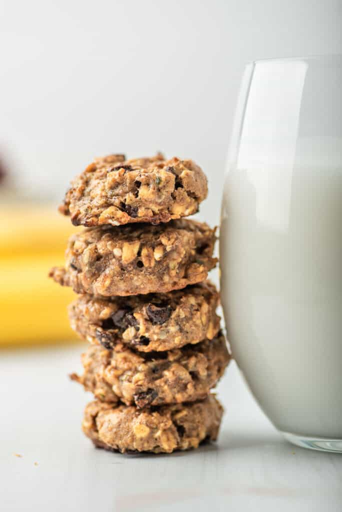 Cookies stacked next to a large glass of milk.