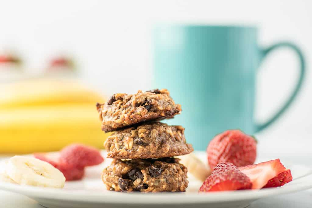 3 breakfast cookies on a plate with fruit.