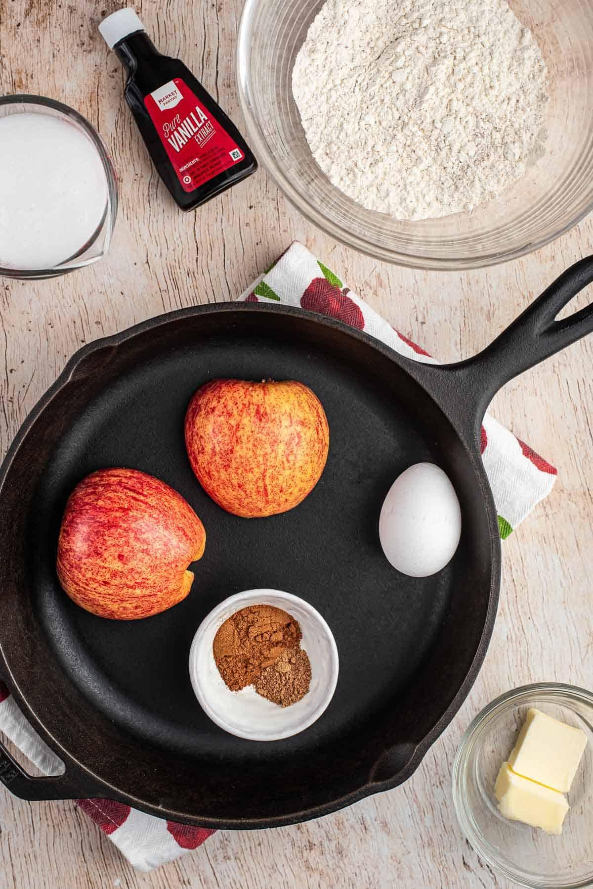 Apple pancake ingredients and a black skillet.