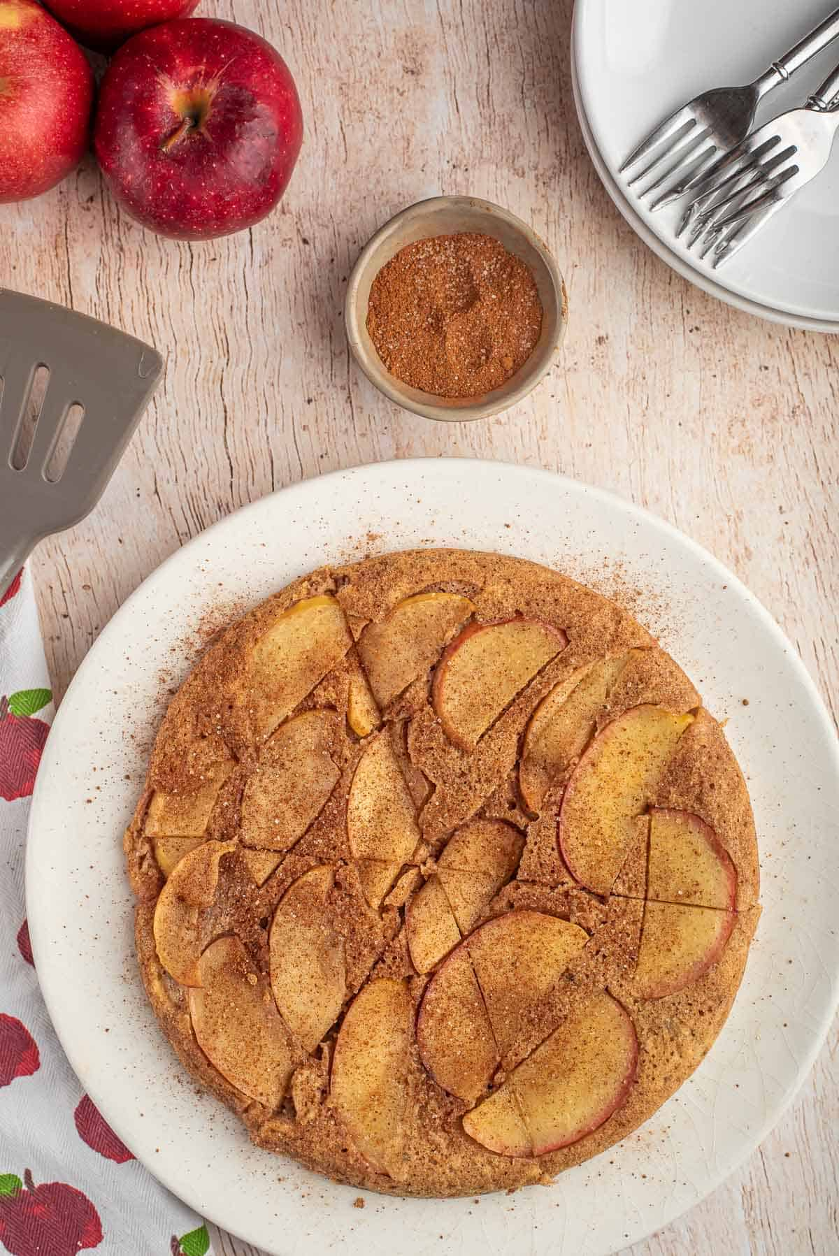 Overhead view of large apple pancake, cut into wedges.