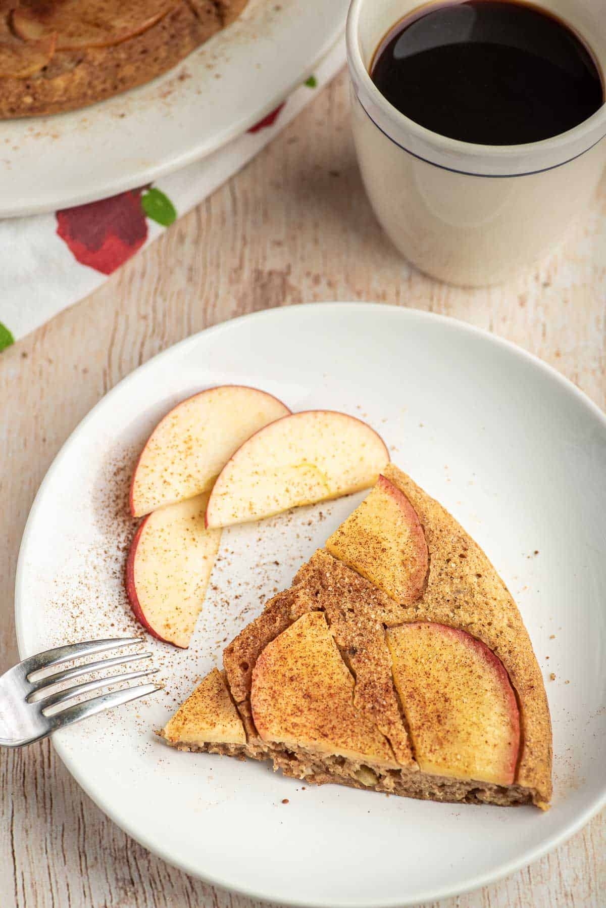 Slice of apple pancake on a white plate with apple slices. Coffee in background.