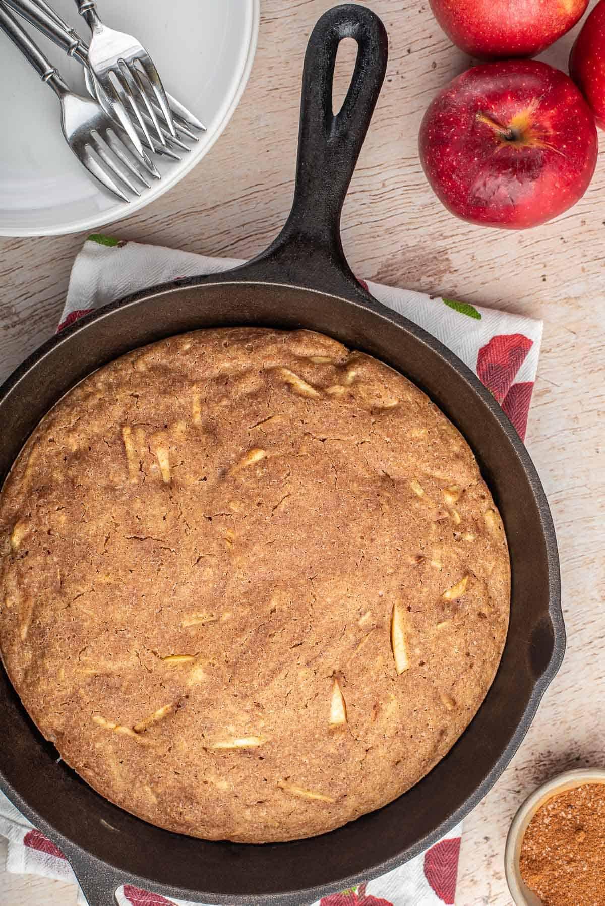 Overhead view of apple pancake in a black skillet.