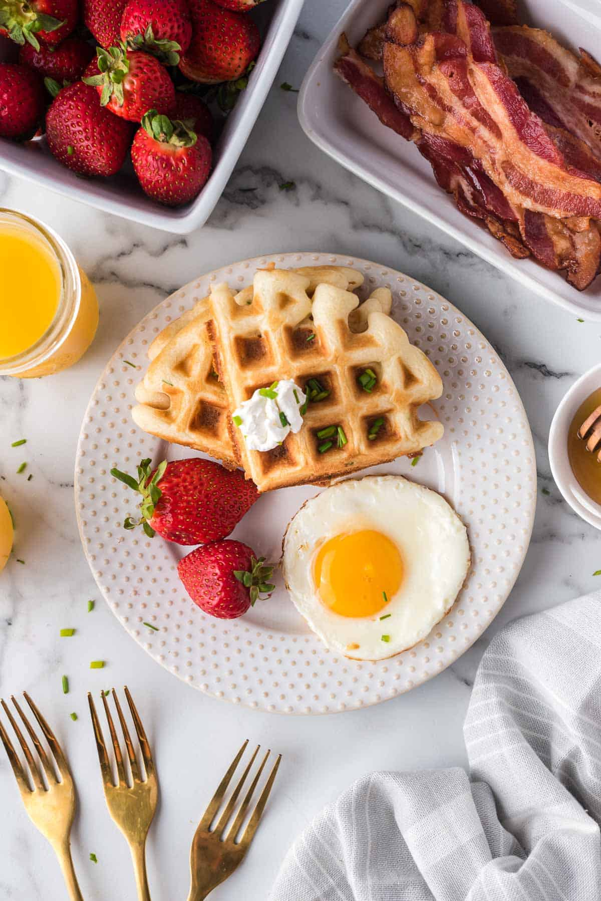 Overhead view of a plate with waffles, strawberries, and an egg.