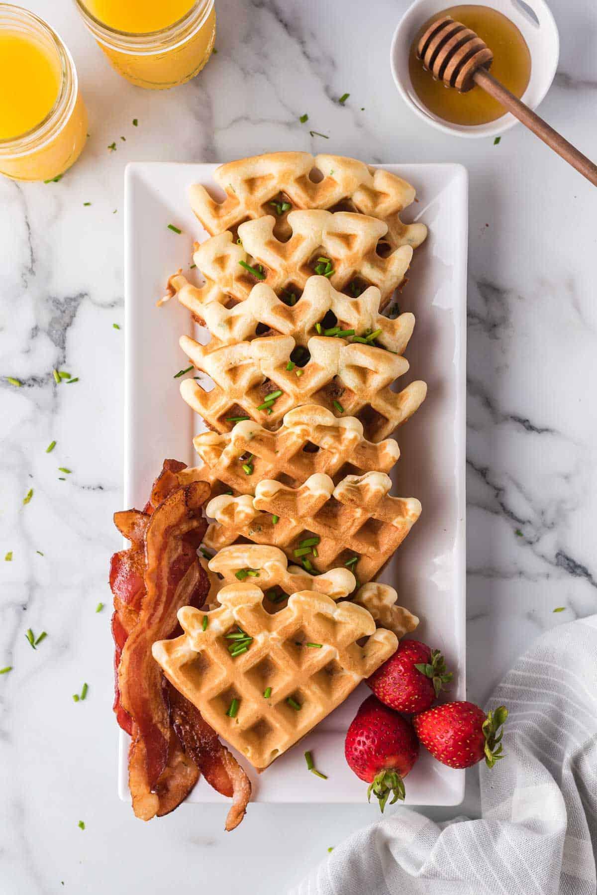 Savory waffles on a tall, thin white platter.