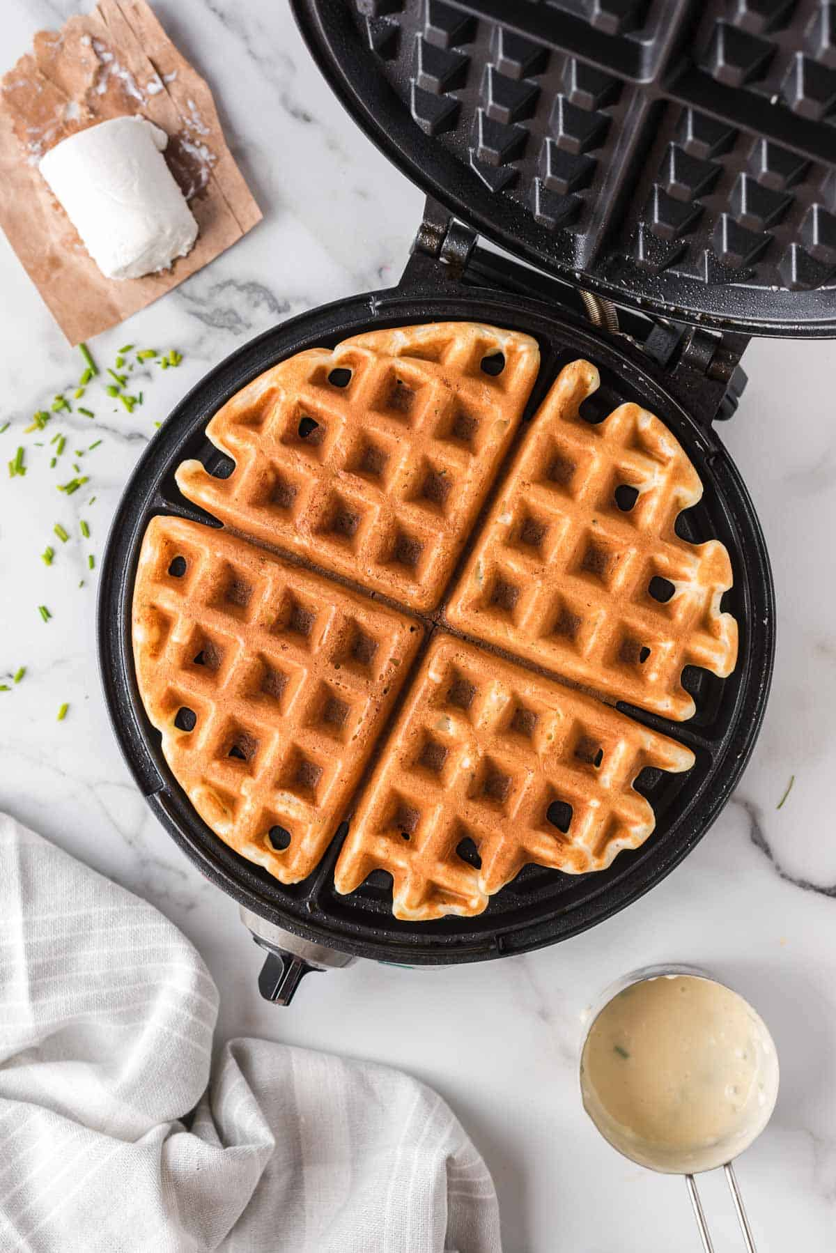 Overhead view of a waffle in a waffle iron, surrounded by ingredients.