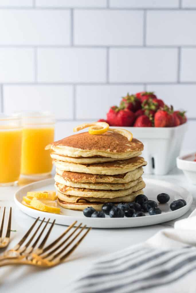 Stack of pancakes with blueberries on the side.