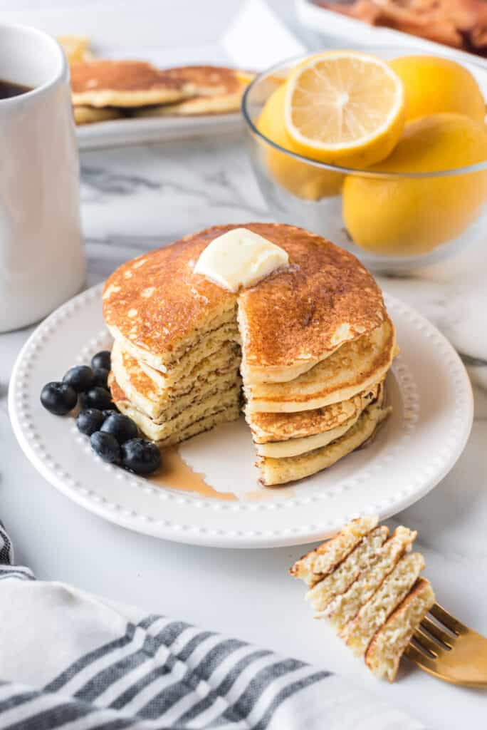 Stack of pancakes with a slice cut out.