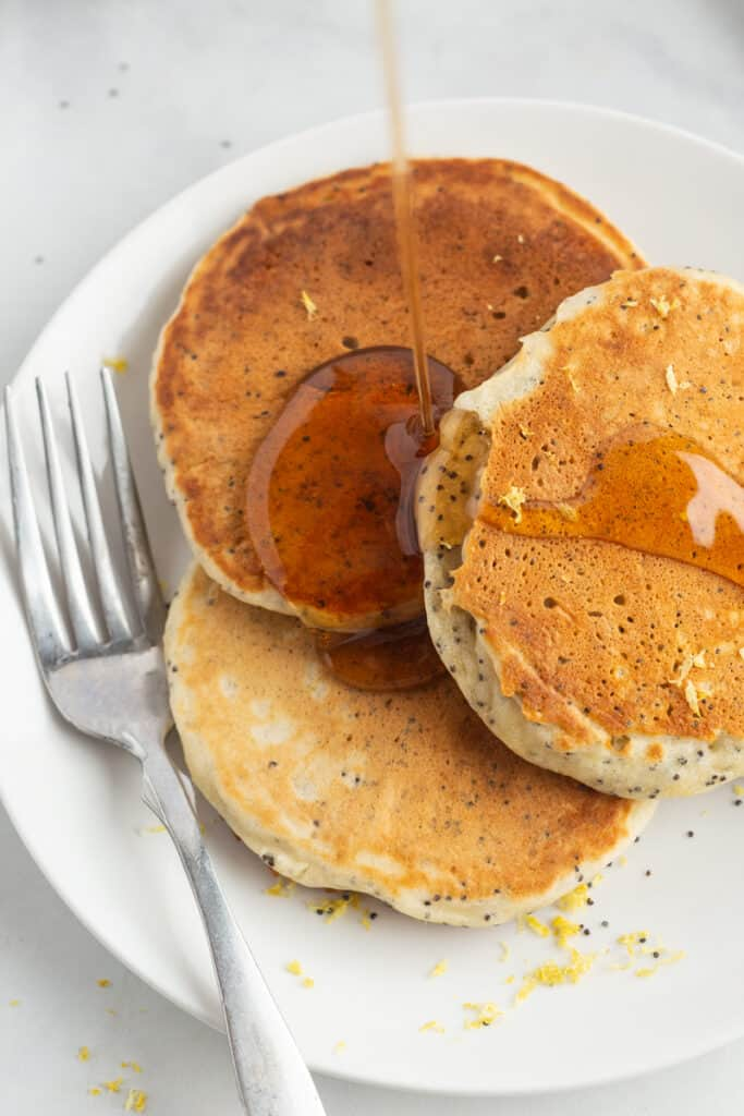 Three lemon pancakes on a plate with syrup and a fork.