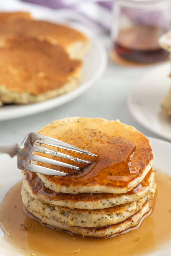 Stack of pancakes with syrup, a fork digging in.