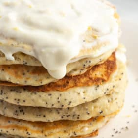 Stack of lemon poppyseed pancakes on a white plate, with a cream cheese glaze.