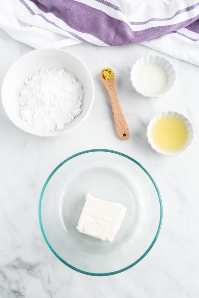 Overhead view of ingredients: cream cheese, powdered sugar, lemon juice and zest, milk.