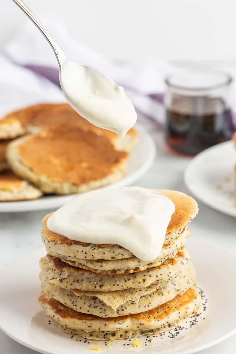 Lemon cream cheese glaze being spooned onto pancakes.