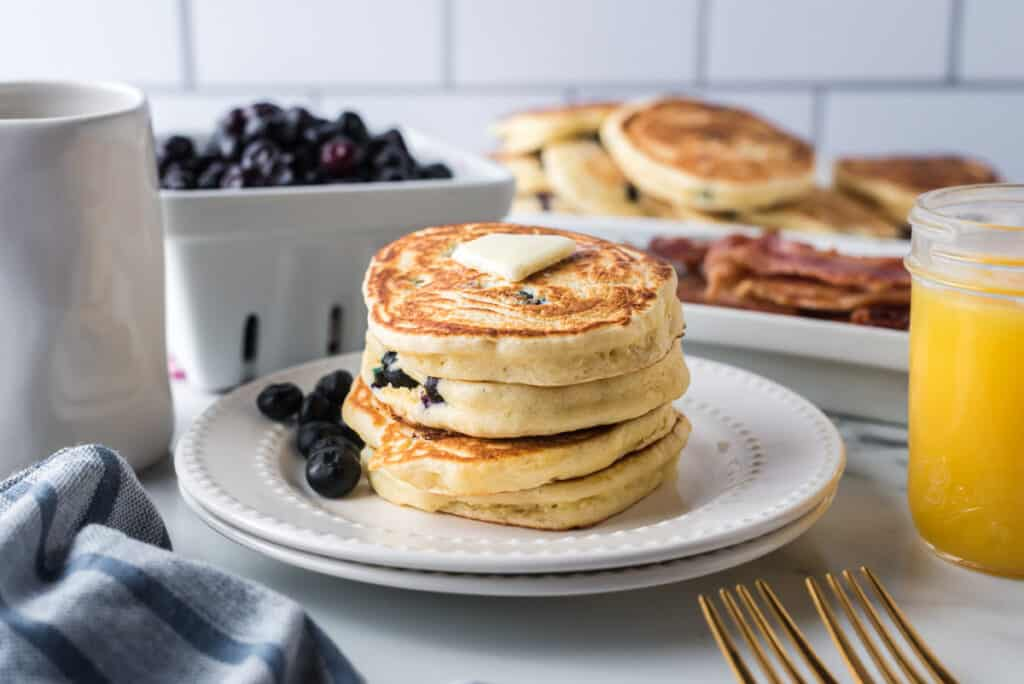 Short stack of pancakes with blueberries and butter.