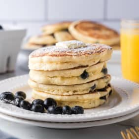 Stack of blueberry pancakes on a white plate, with fresh blueberries. Orange juice in background.