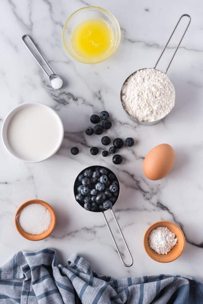 Overhead view of ingredients needed to make blueberry pancakes, on a white marble background.