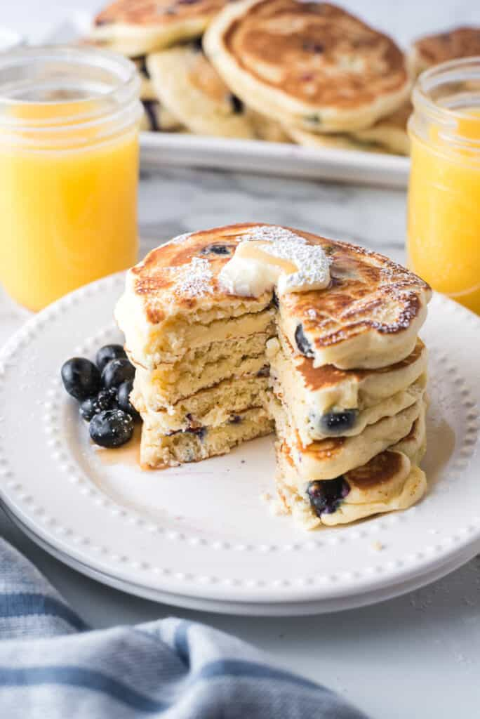 Stack of pancakes with slice cut out to show texture and blueberries inside.