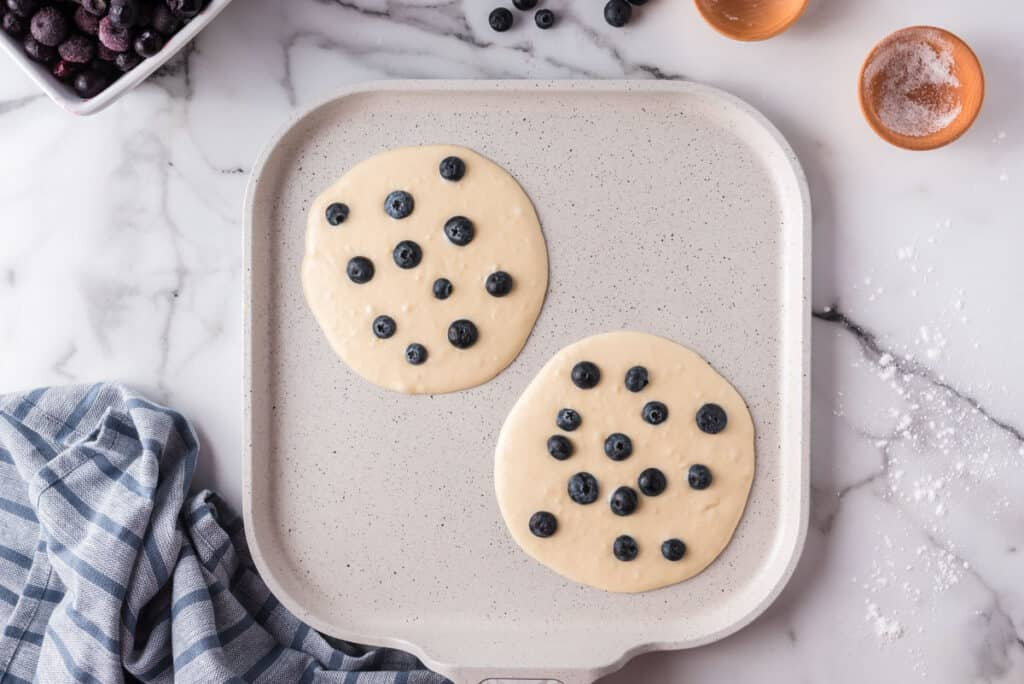 Uncooked blueberry pancakes on a griddle.