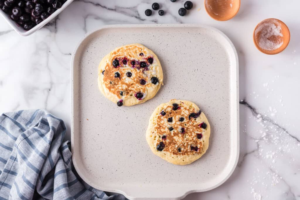 Pancakes with blueberries on a griddle.