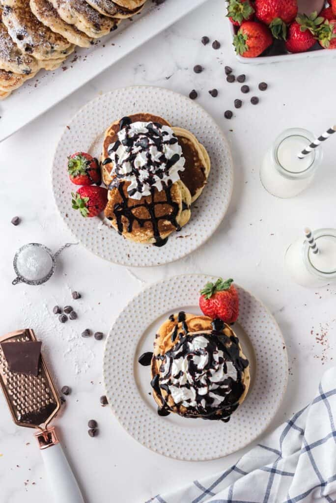 Overhead view of two plates of whipped cream and chocolate topped pancakes.