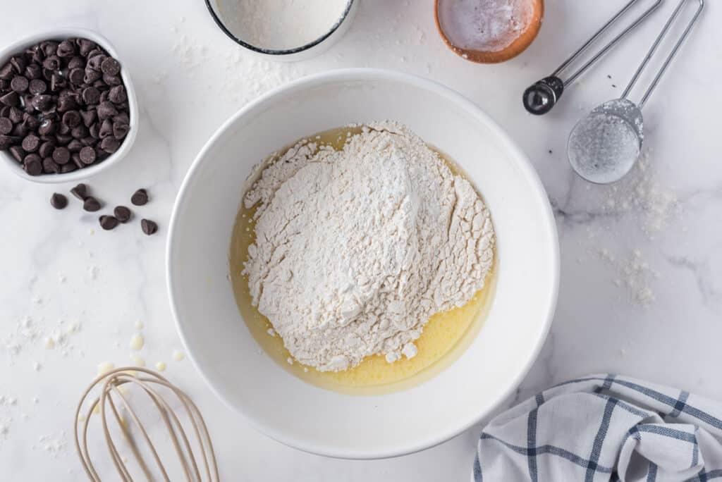 Pancake dry ingredients being added to wet ingredients in white mixing bowl.
