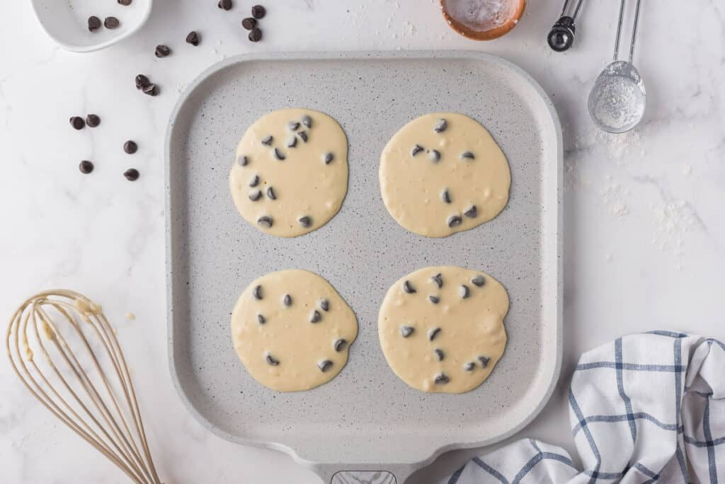 Uncooked chocolate chip pancakes on a griddle.