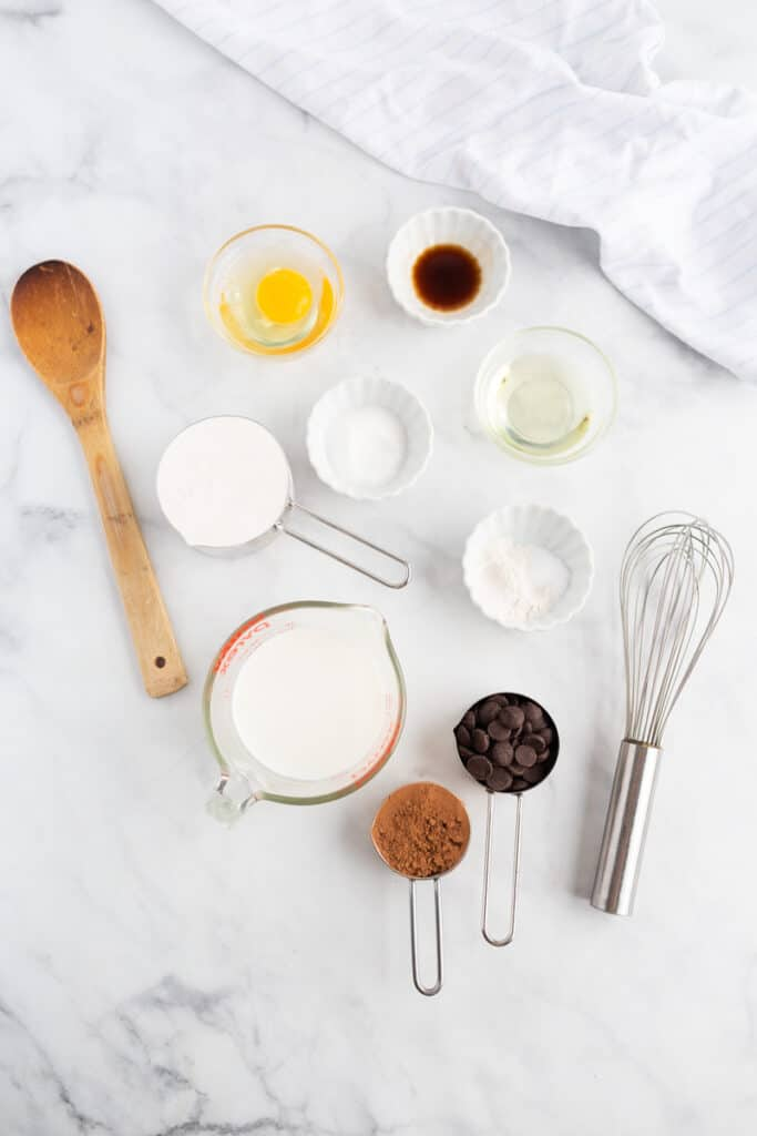 Ingredients for chocolate chocolate chip pancakes on a white marble background.
