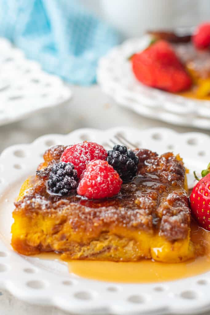 Slice of french toast with syrup and berries on a white plate.