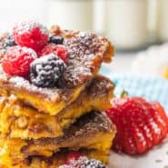 Stack of creme brulee french toast on a white plate with berries and powdered sugar.
