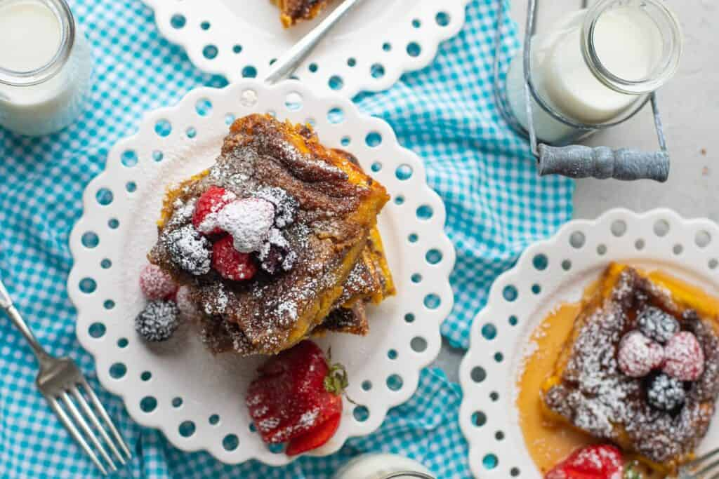 Plated french toast, white plates, blue linen, milk and berries also present.
