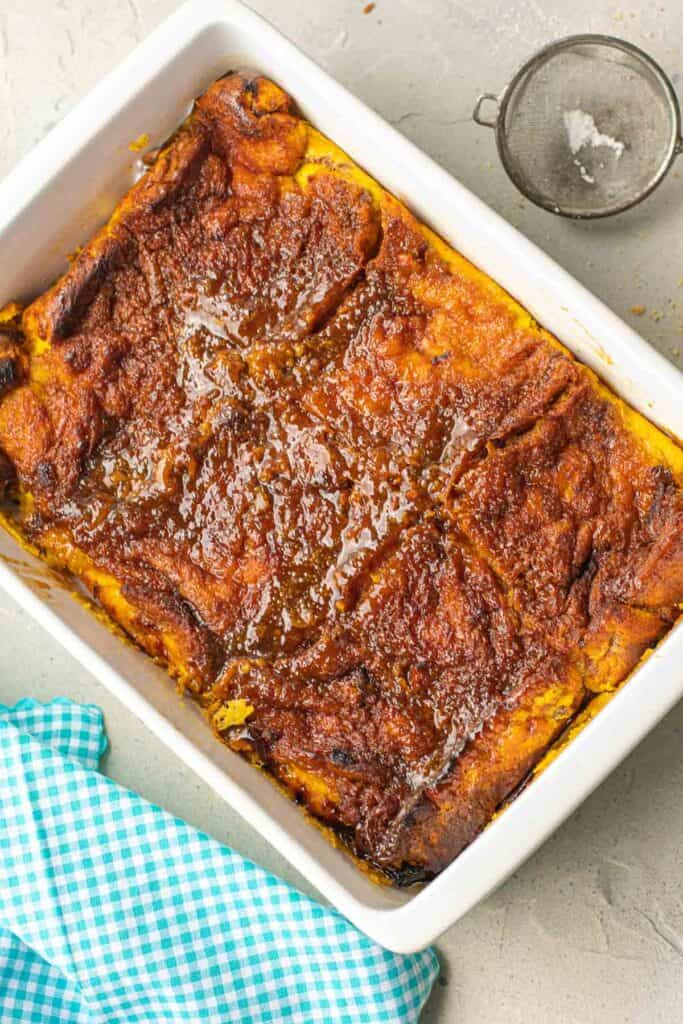 Baked french toast in a white baking dish, a blue cloth nearby.