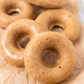 Pile of light brown donuts on a brown paper.