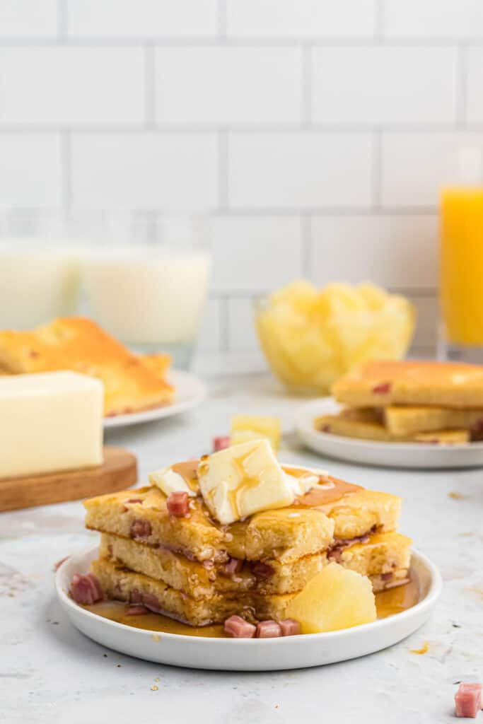 stack of pancake slices with pineapple and ham, on a white plate. Additional breakfast items in the background.