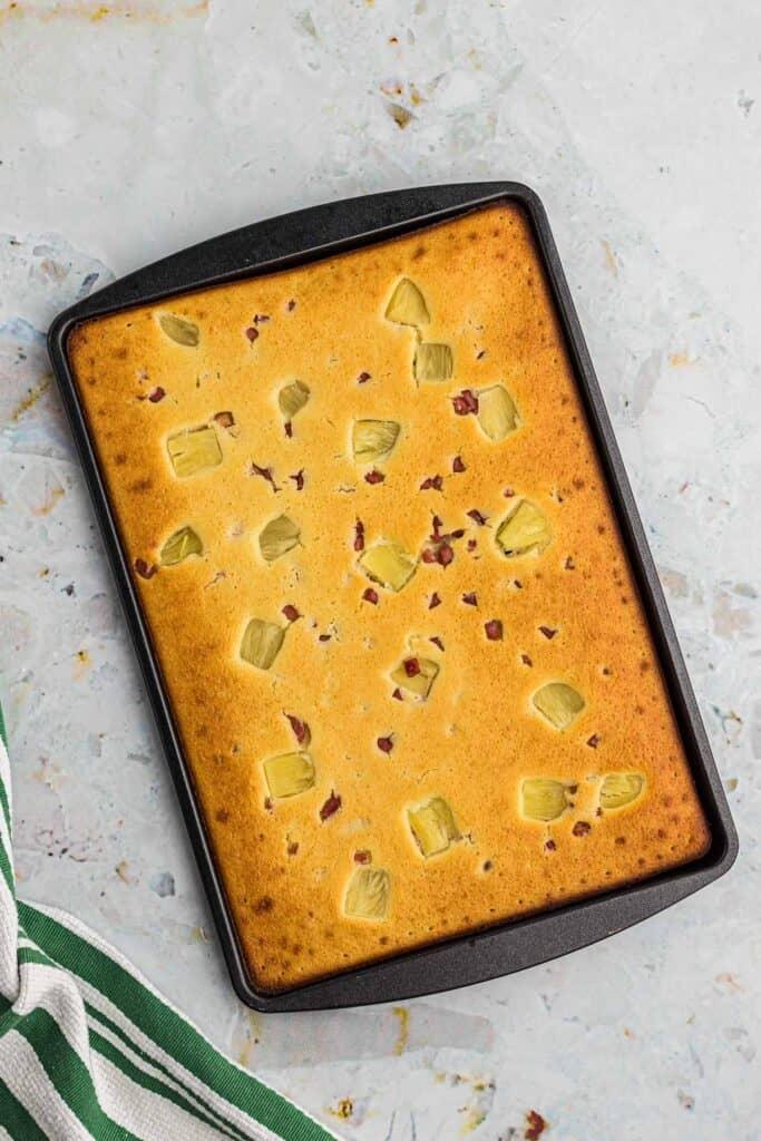 Baked pancake batter and toppings on a dark metal sheet pan.