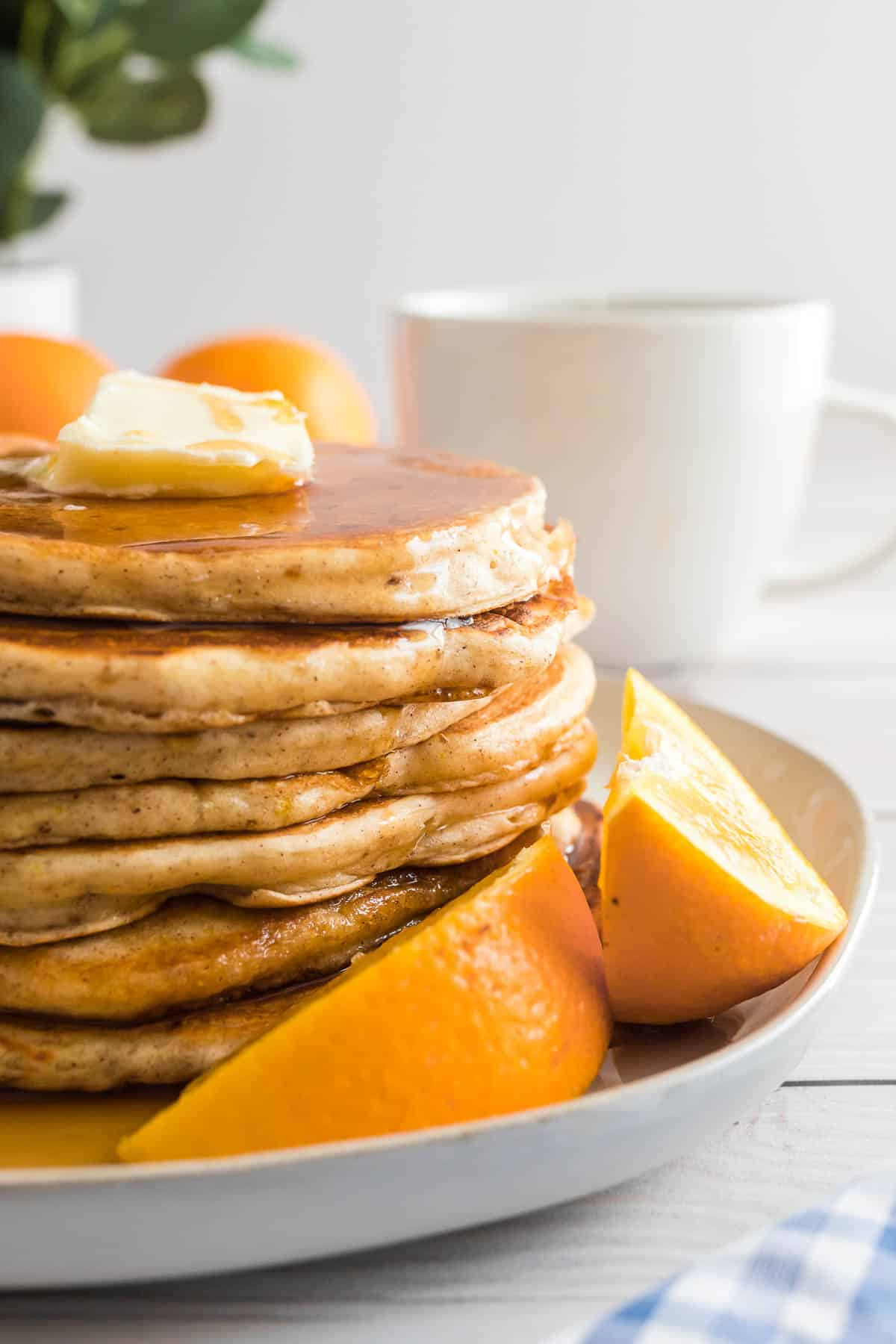 Stack of orange buttermilk pancakes on a plate with orange wedges.