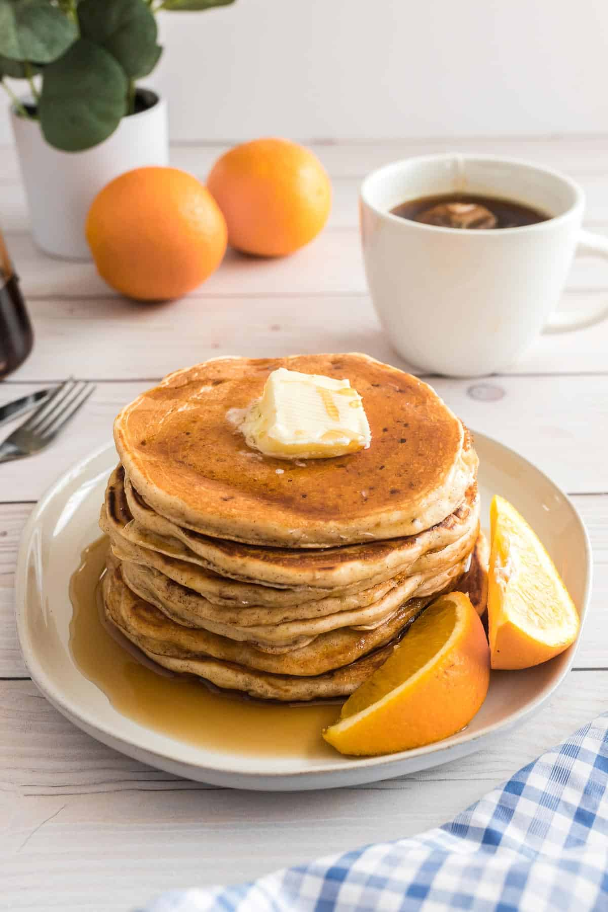 Pancakes and syrup on a plate with orange wedges, coffee and oranges in the background.