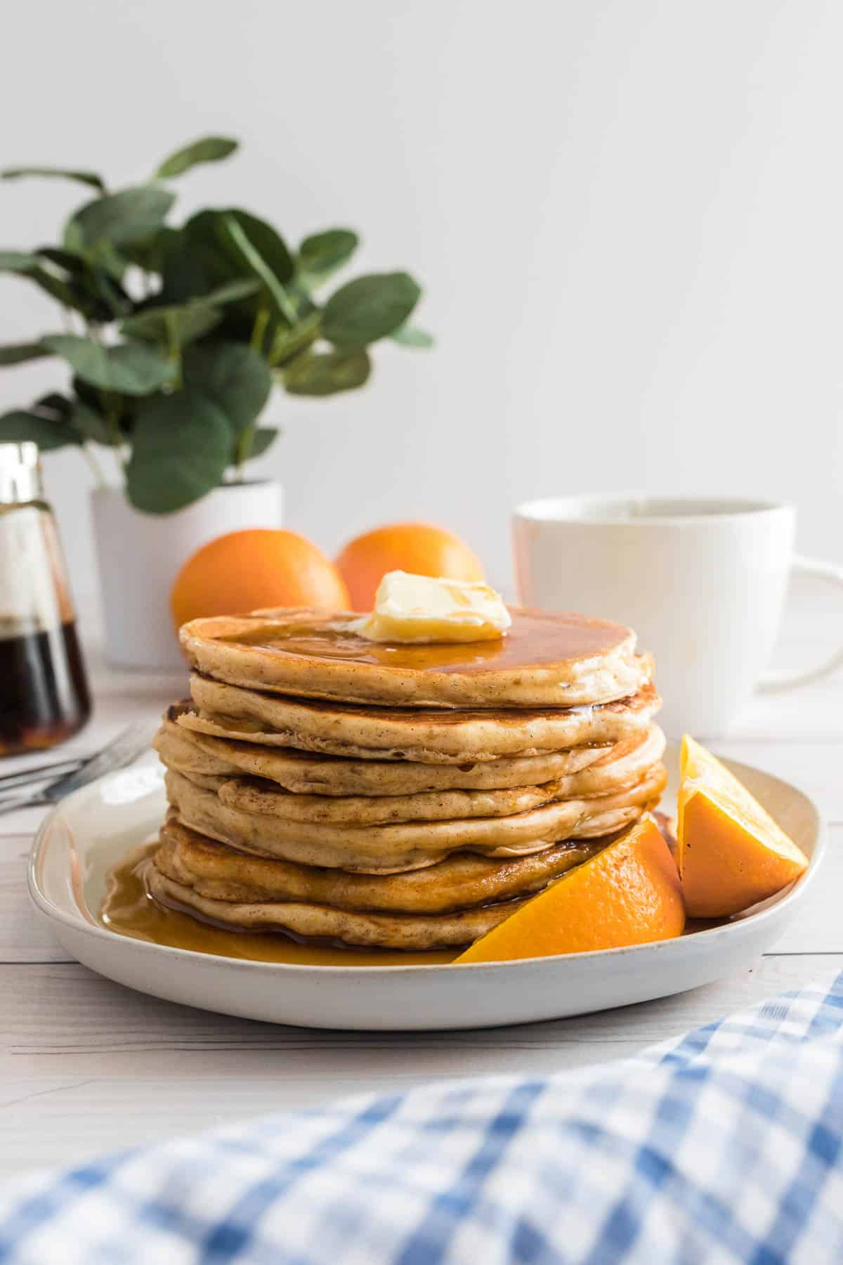 Stack of orange pancakes on a white plate.