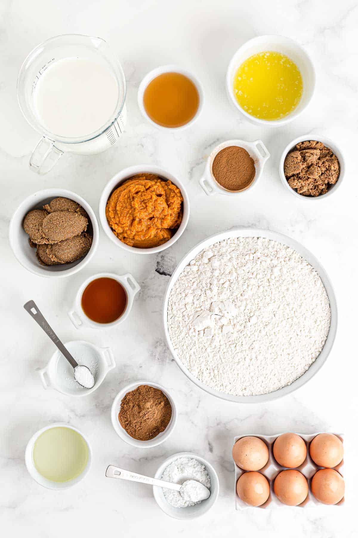 Ingredients for pumpkin sheet pan pancakes, on a white surface.