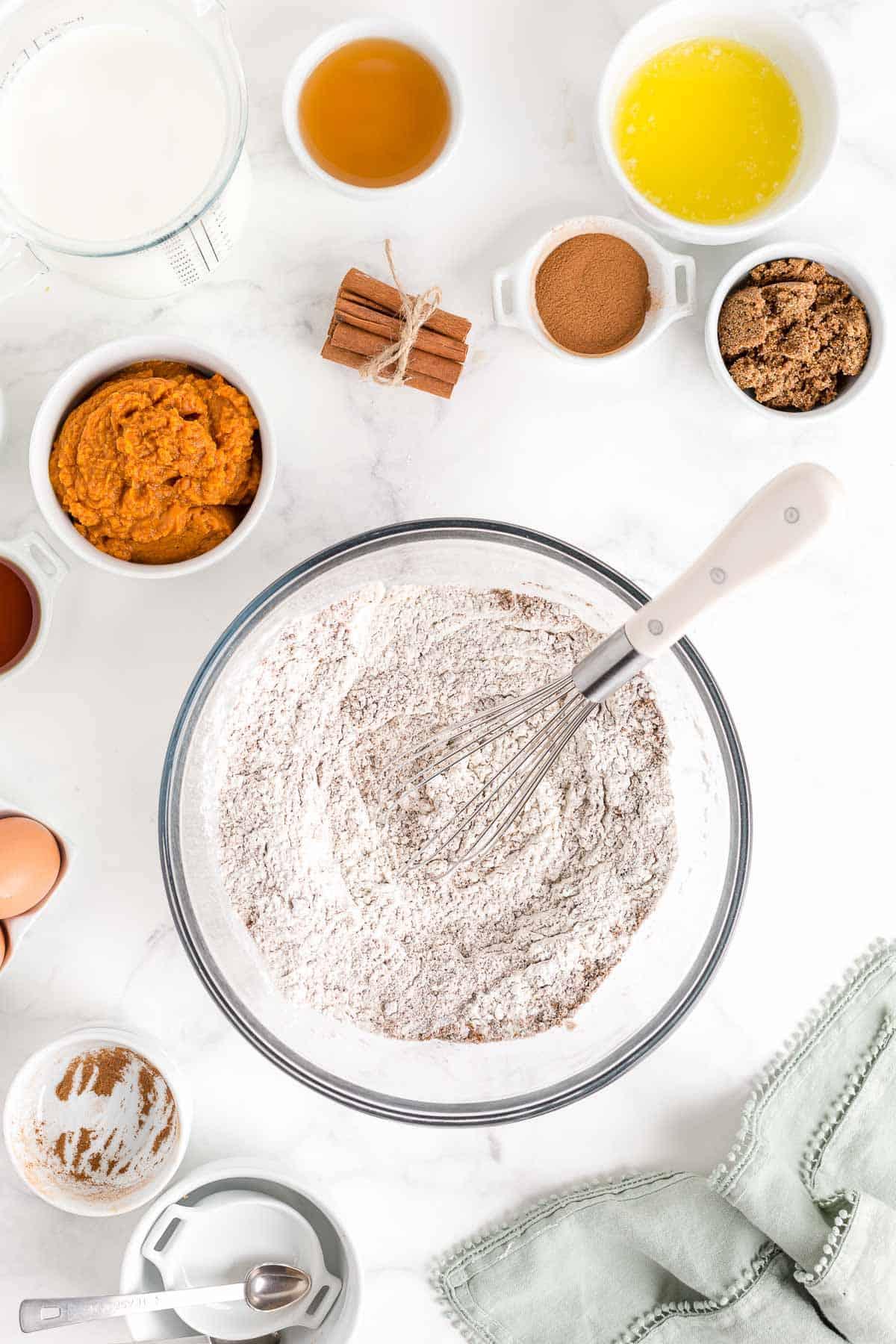Dry ingredients for pumpkin pancakes in a bowl, wet ingredients surrounding it.