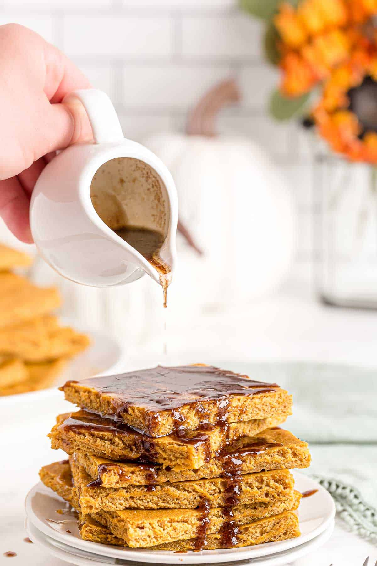 Stack of pumpkin sheet pan pancake slices, being topped with cinnamon butter drizzle.