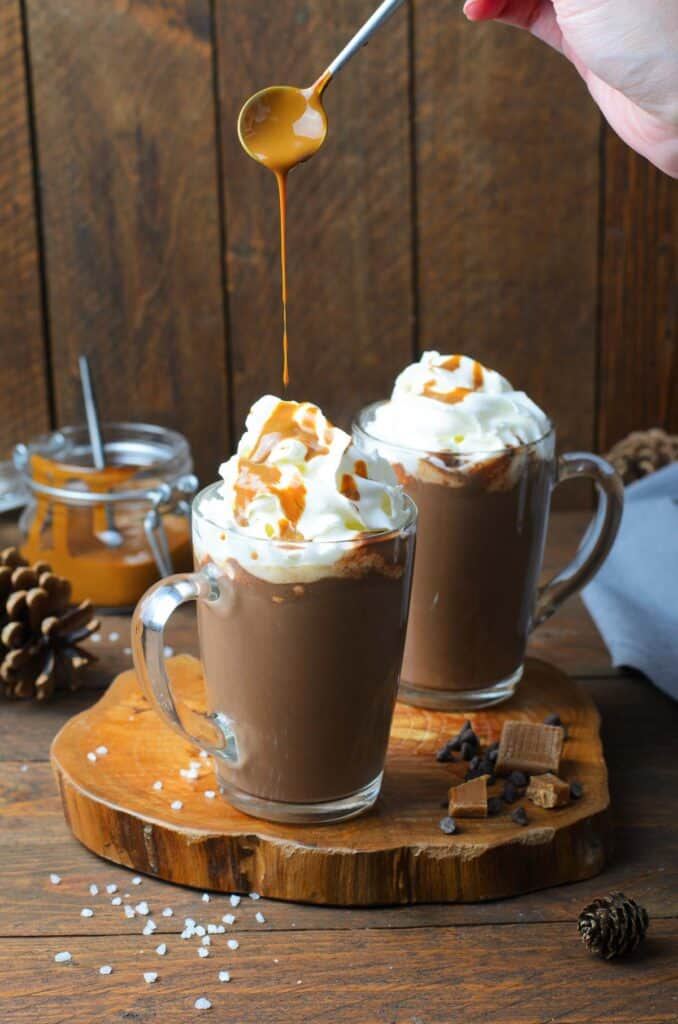 Two clear mugs of hot chocolate topped with whipped cream being drizzled with caramel sauce