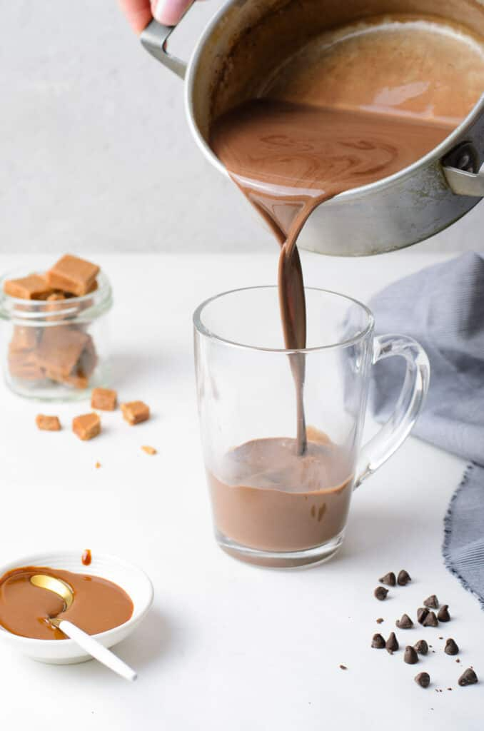 Hot chocolate being poured from a saucepan into a clear glass mug.